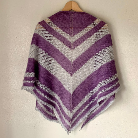 Image of a striped shawl draped over a wooden coat hanger. The shawl has stripes of varying depths with an alternating pattern of plain purple sections and silver lace sections.