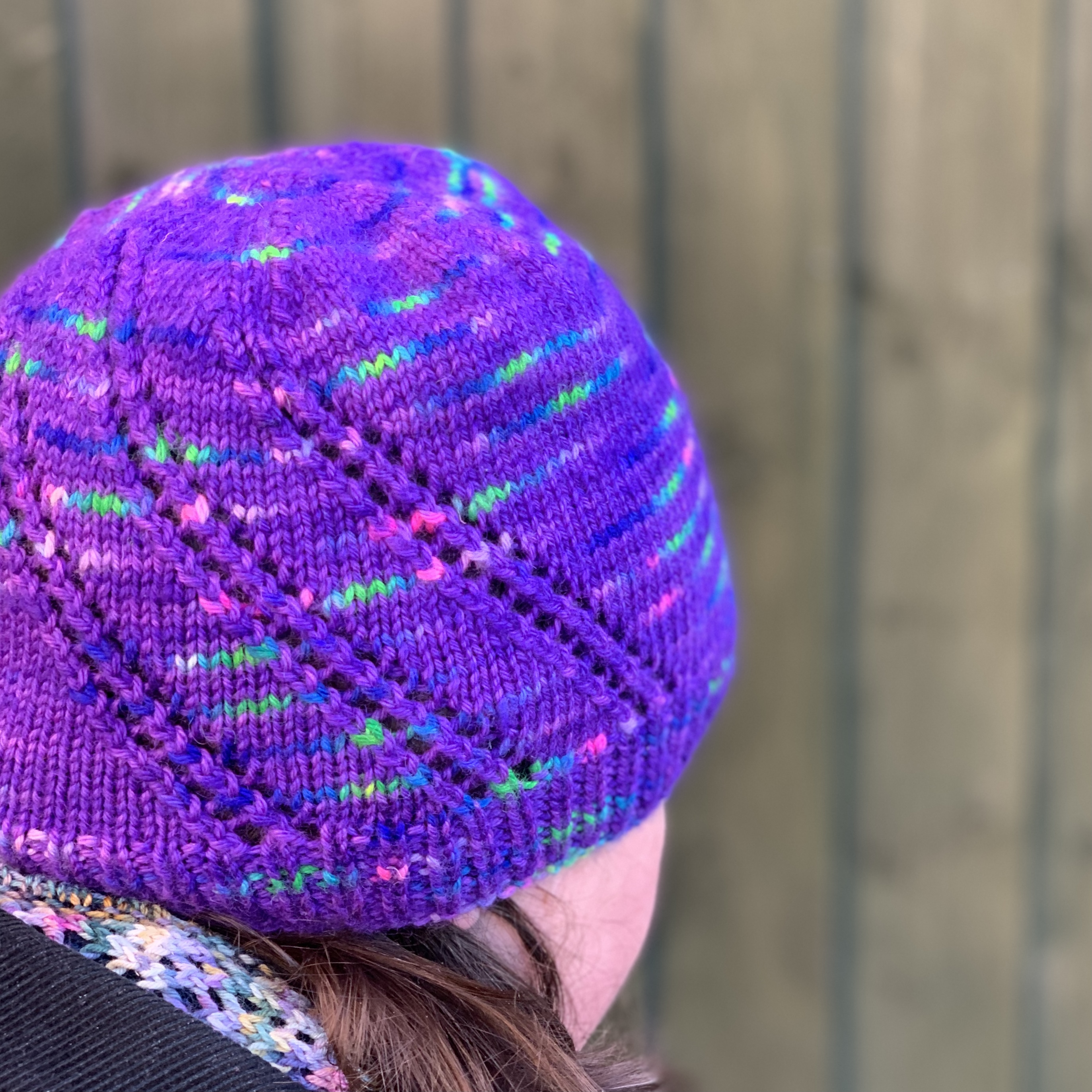 Northern Lights hat. Stocking stitch hat with 3 diagonal lace strips. Yarn used is purple with flashes of bright green, blue and pink.