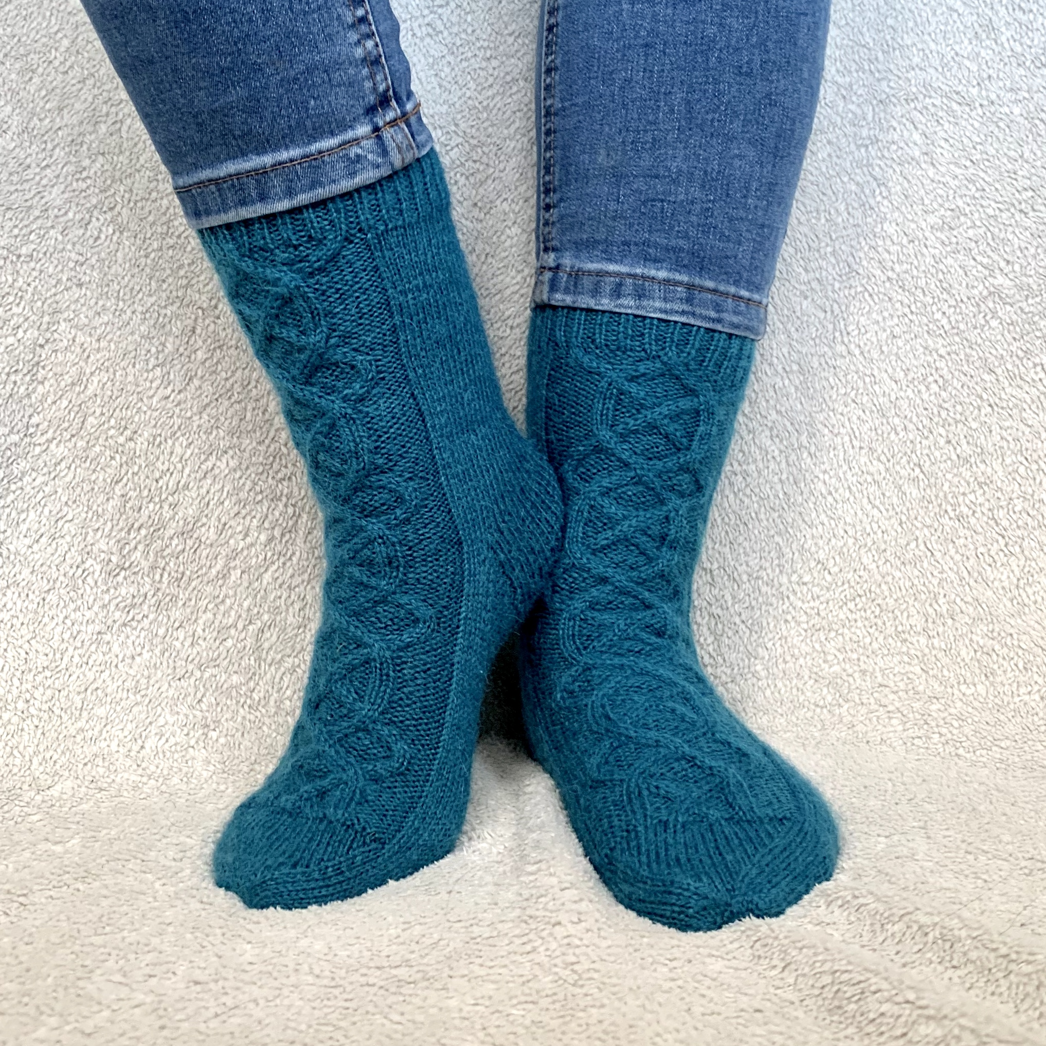 Borealis socks. Teal wool socks with cable detail running up the top of the foot and front of the leg.