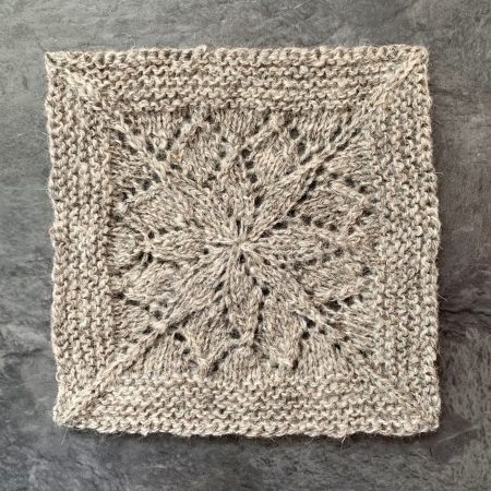 A blanket square with a lace flower motif in the centre surrounded by a garter stitch border. Pattern is knit in grey North Ronaldsay wool and is from the pattern Vivid by Tin Can Knits.