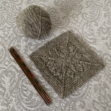 A grey wool blanket square with lace motif in the centre sits next to a small ball of grey wool and a set of double pointed needles.