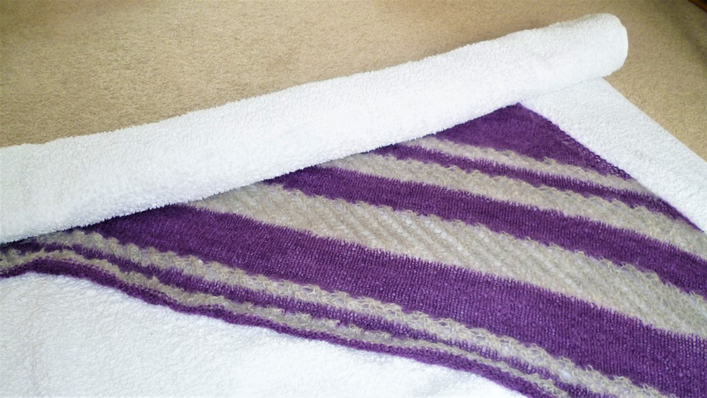 How to block your knits. Lace shawl being rolled up in a towel. Edge of the shawl is still curling up.