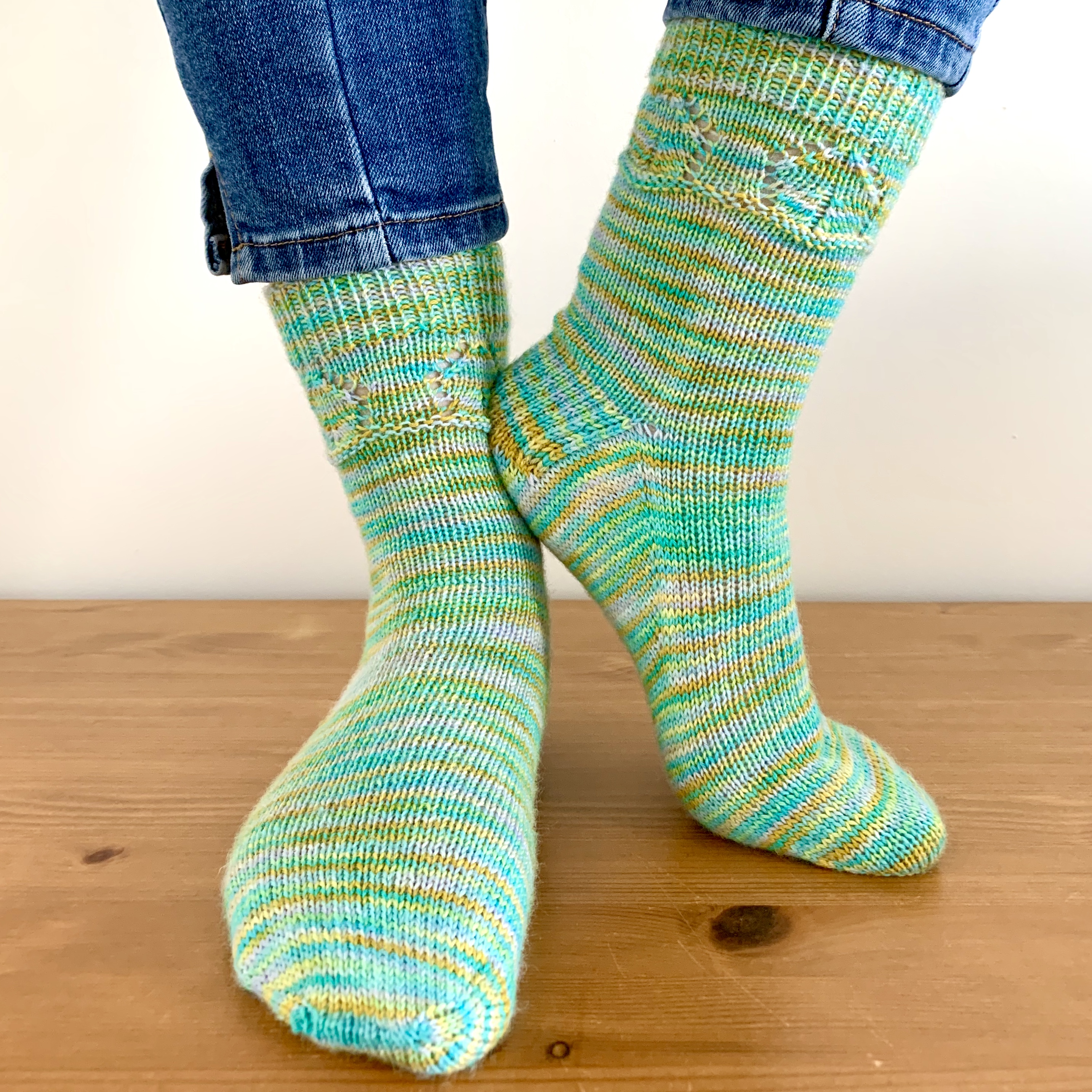 Birdhouse Socks. Plain socks in turquoise, yellow and white self-striping yarn. Features a birdhouse motif around the top of the leg.