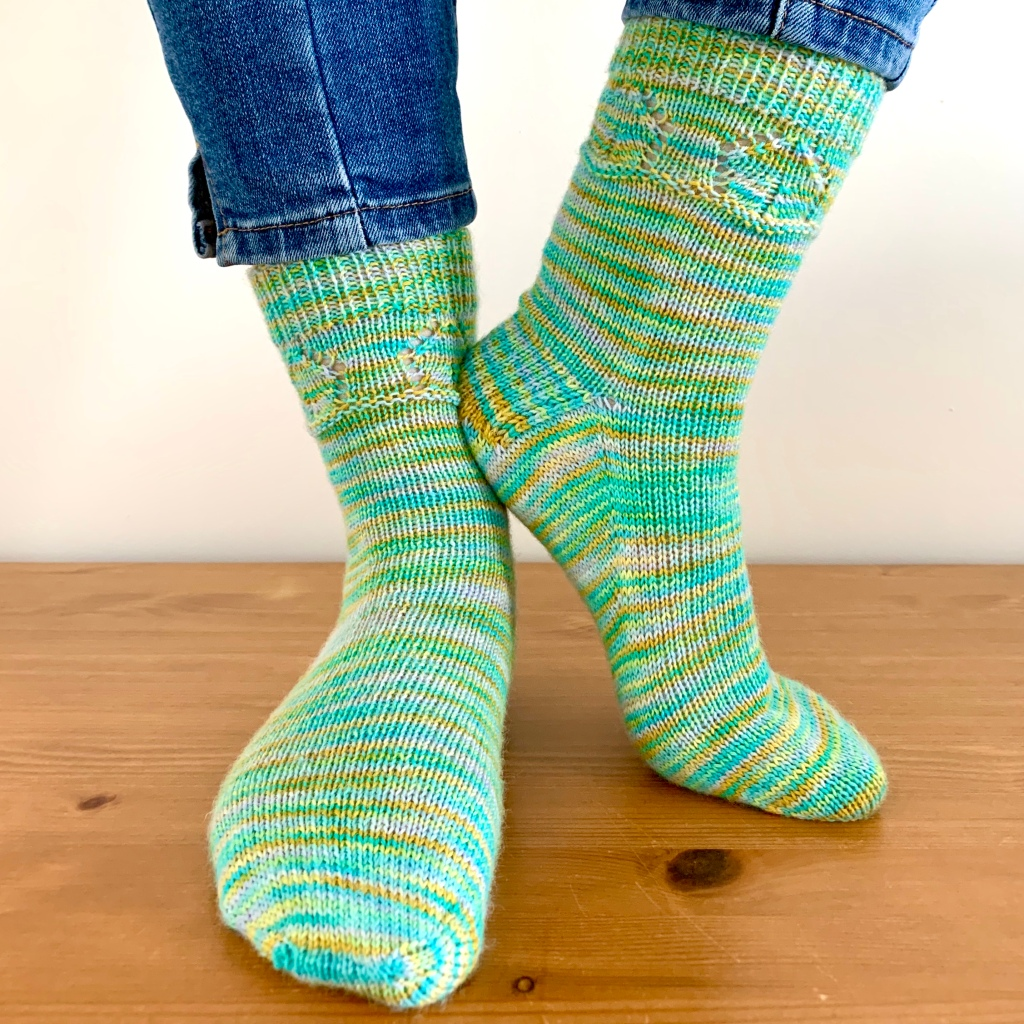 Striped socks in pale green, white and gold. Plain stocking stitch with small birdhouse detail below the ribbed cuff, modelled on a wooden floor against a grey background.