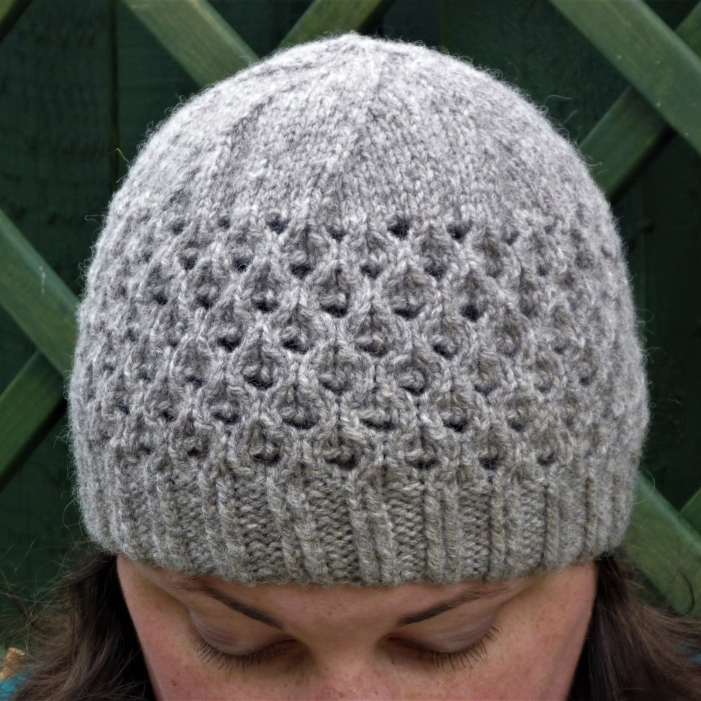 The Lady Jane hat in grey wool with a ribbed brim and peacock lace up to a plain stocking stitch crown. Lace is a series of faux circular cables with large lace holes in their centre. Hat is modelled against a green background which model looking down.