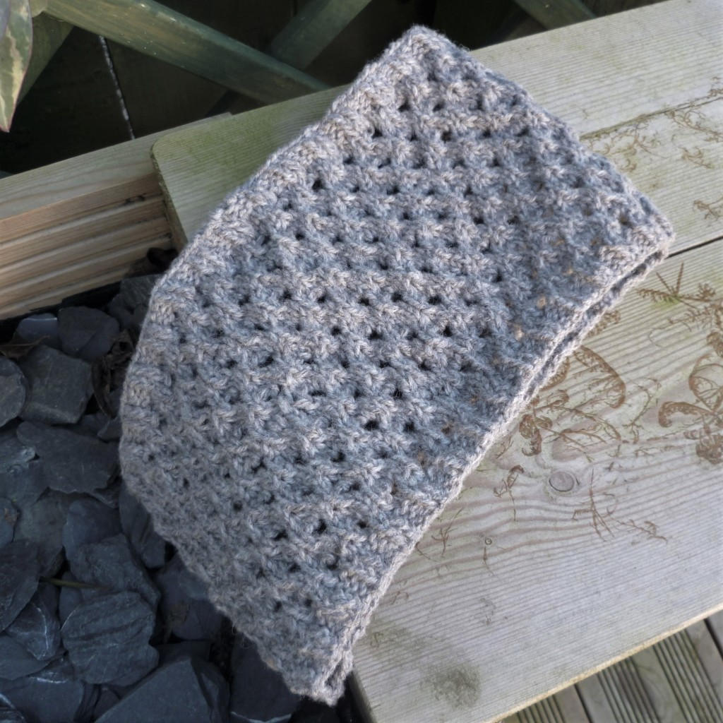 The Lady Jane cowl with peacock lace. The faux circle cables with large holes in their centre is the main stitch pattern with a thin ribbed edging top and bottom. Grey wool cowl is draped over a wooden bench and dark grey pebbles.