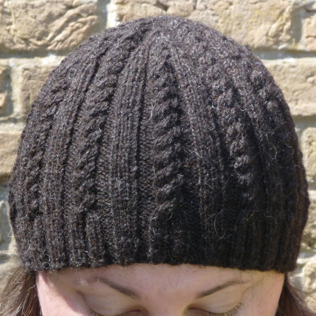 The Close to Home hat with cable and rib pattern running from brim to crown. This brown wool hat is being modelled against a pale brick wall in the sunshine.