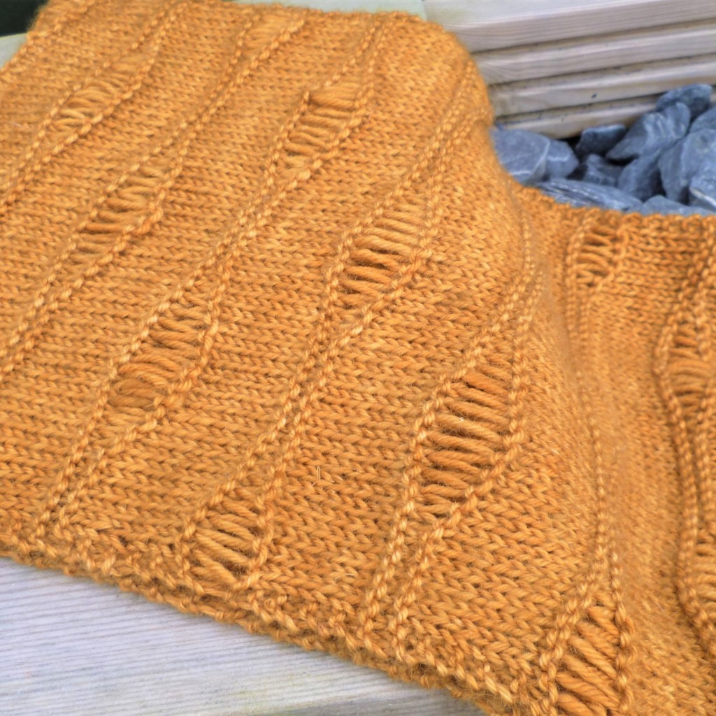 The Spring Dawn cowl in orange wool is a wide cowl with oval waves of long dropped stitches on a stocking stitch background. Cowl is draped over a pale wooden bench and dark grey pebbles.