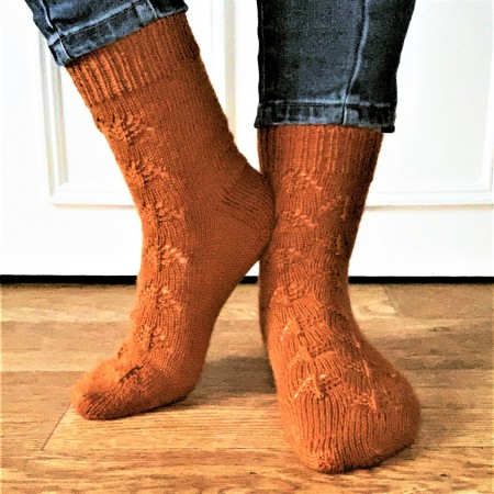 Forest floor socks. Burnt orange wool/nylon socks. Mostly knit plain with a repeating pine cone motif running up the top of the foot and front of the leg.