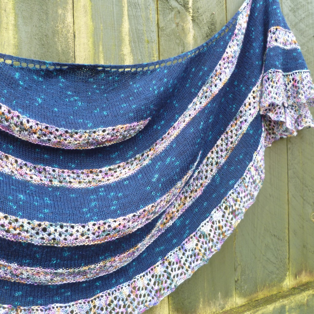 The Australis shawl with multicoloured short row sections using simple lace, against a dark blue stocking stitch background with lighter blue speckles. Crescent shaped shawl is hung against a green fence.