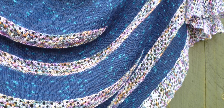 Australis Shawl. A blue stocking stitch background with lace short rows knit in a speckled pink/purple yarn. Shawl has a lace knit on edging.