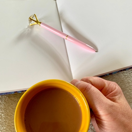 My hand holding a cup of tea while contemplating what to write in the notebook in front of me, the pen laying across the two open pages.