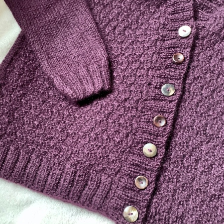 The front of a purple cardigan. The sleeve is laid across the front and brown and shell coloured buttons are fastened up the centre.