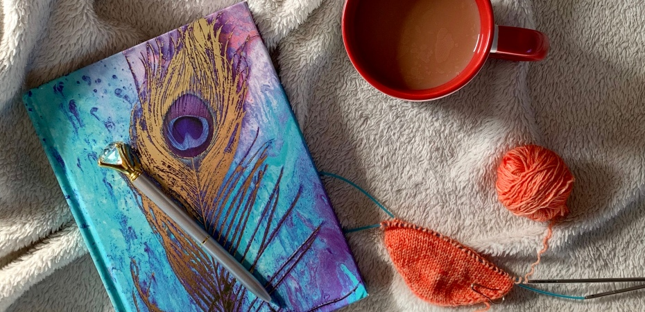 Image shows a pen sat on a peacock feather journal, to the right is a mug of tea and the beginnings of a toe-up sock