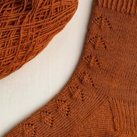 Close up of a single burnt orange hand knit sock, sitting to the left is the half used ball of the same yarn.