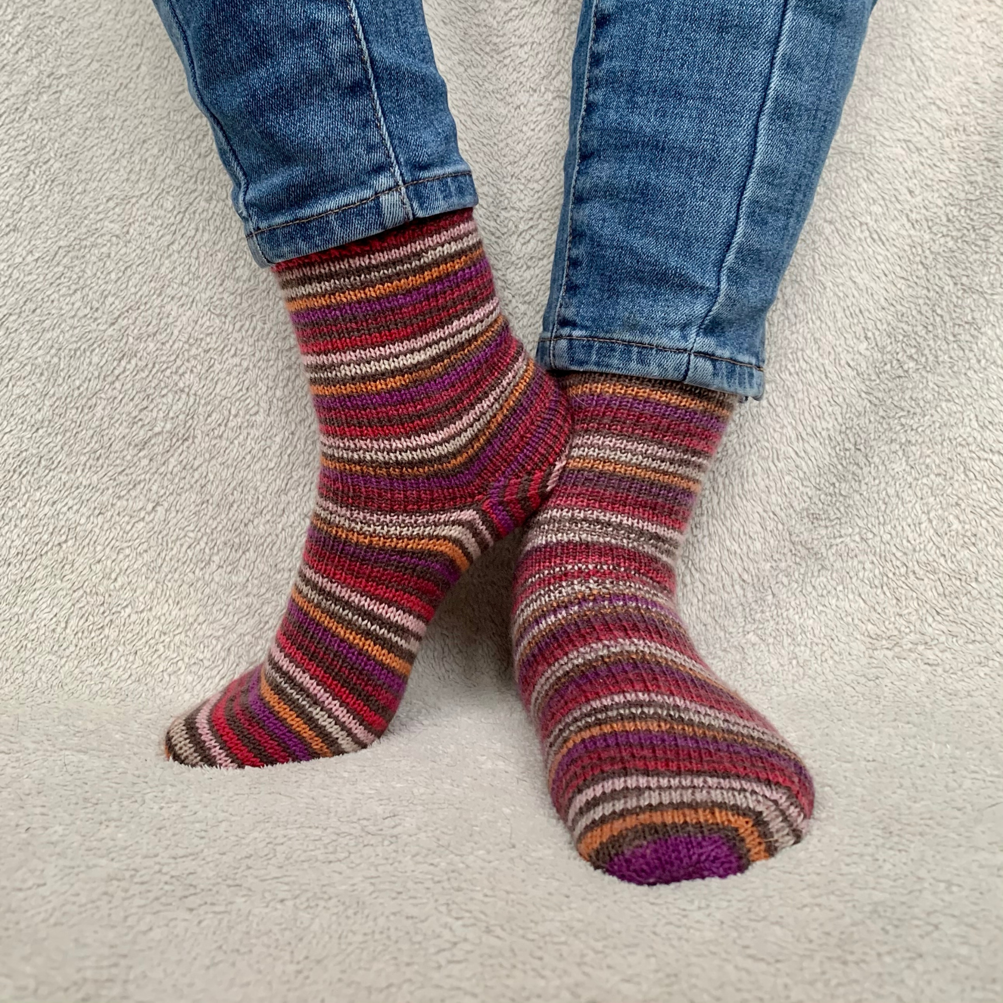Keep It Simple socks. Striped socks in pinks and browns. Modelled with one foot leaning against the other against a cream background