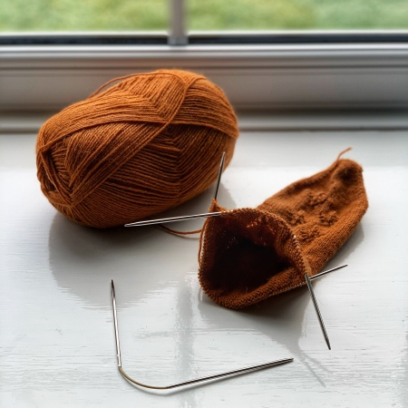A half knit toe-up sock sits next to a large ball of yarn on a white window sill. Socks are shown on a set of flexible double pointed needles.