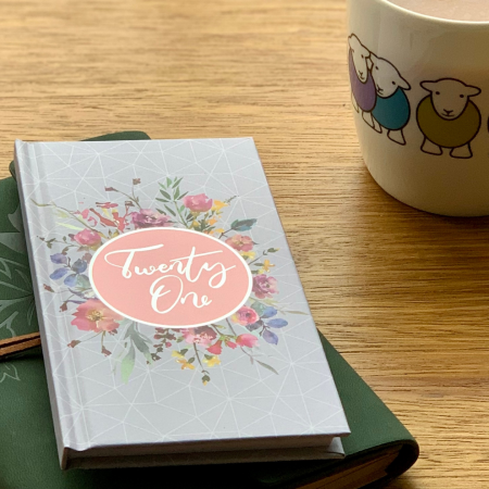 A wooden table with a journal next to a cup of tea. On top of the journal is a 2021 diary.