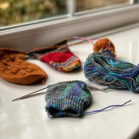 Three half finished socks sit on a window sill. One is a blue/purple self-striping yarn, another is in a burnt orange yarn and the third is a scrappy sock in various reds, blues and oranges.